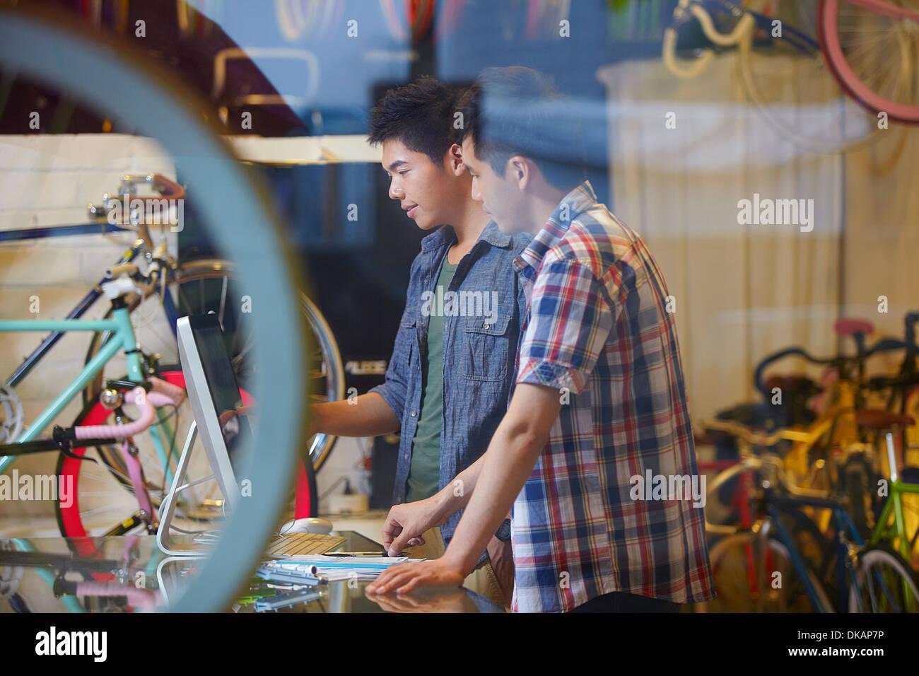 Zwei junge Männer im Fahrradladen mit computer Stockbild