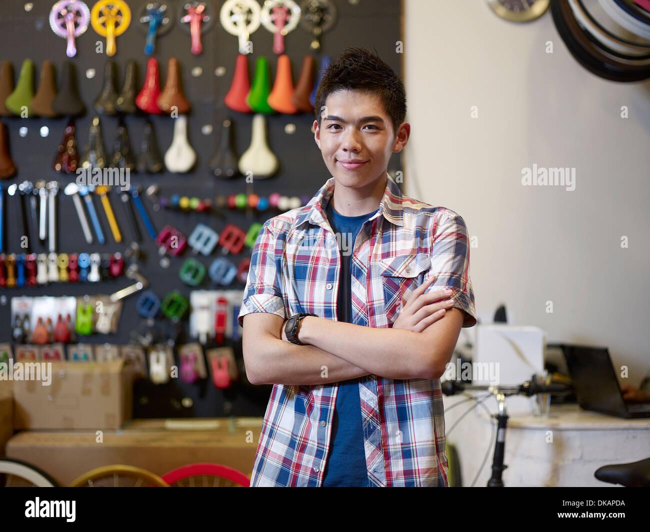 Porträt des jungen Mannes in Bikeshop mit verschränkten Armen Stockbild