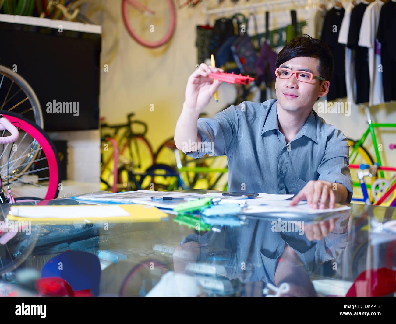 Junger Mann Prüfung Fahrrad Teil im Bike-shop Stockbild