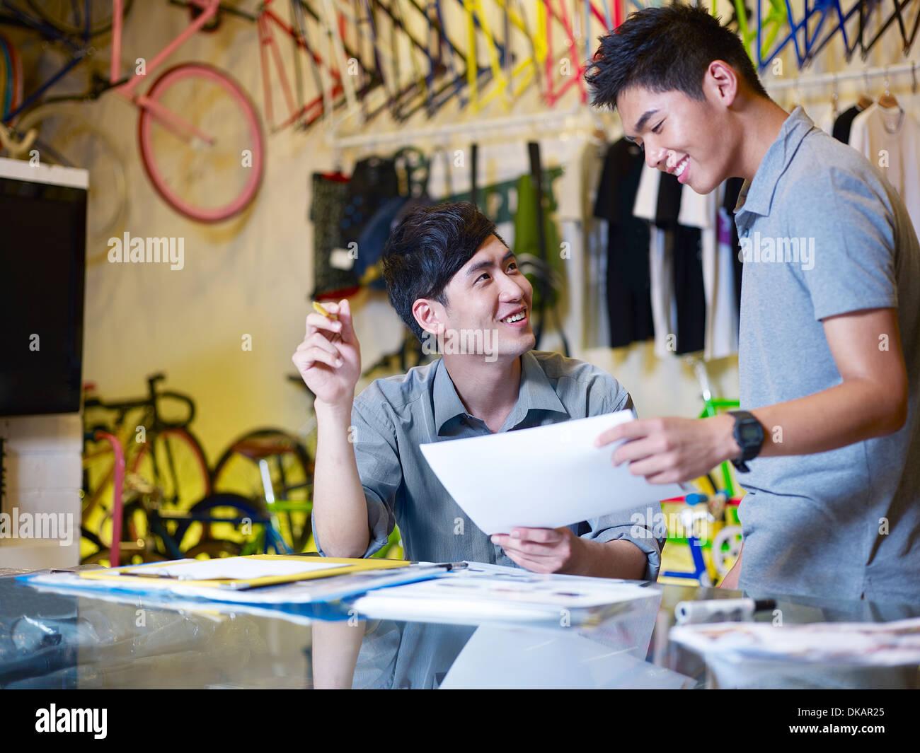 Zwei junge Männer mit Papierkram im Bike-shop Stockfoto