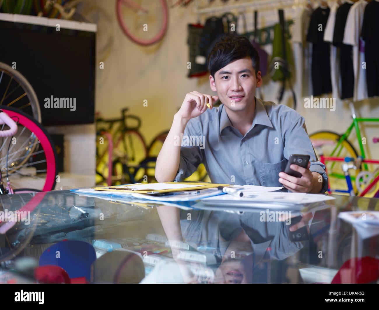 Porträt von junger Mann mit Handy im Bike-shop Stockbild