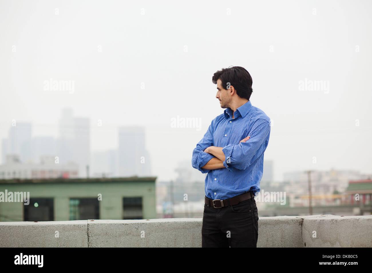 Junger Geschäftsmann mit verschränkten Armen auf Stadt auf dem Dach Stockbild
