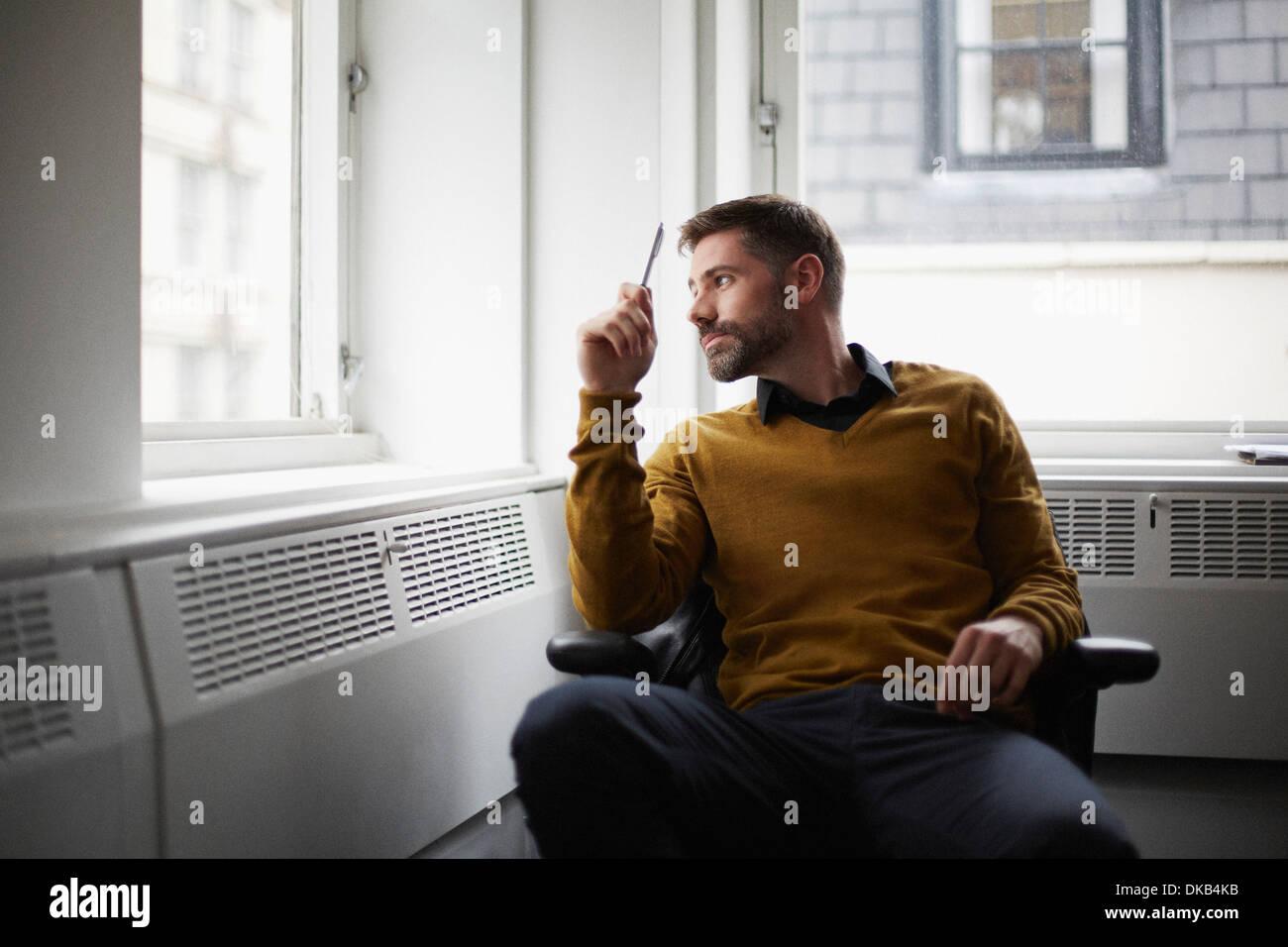 Lässige Geschäftsmann aus Fenster Stockbild