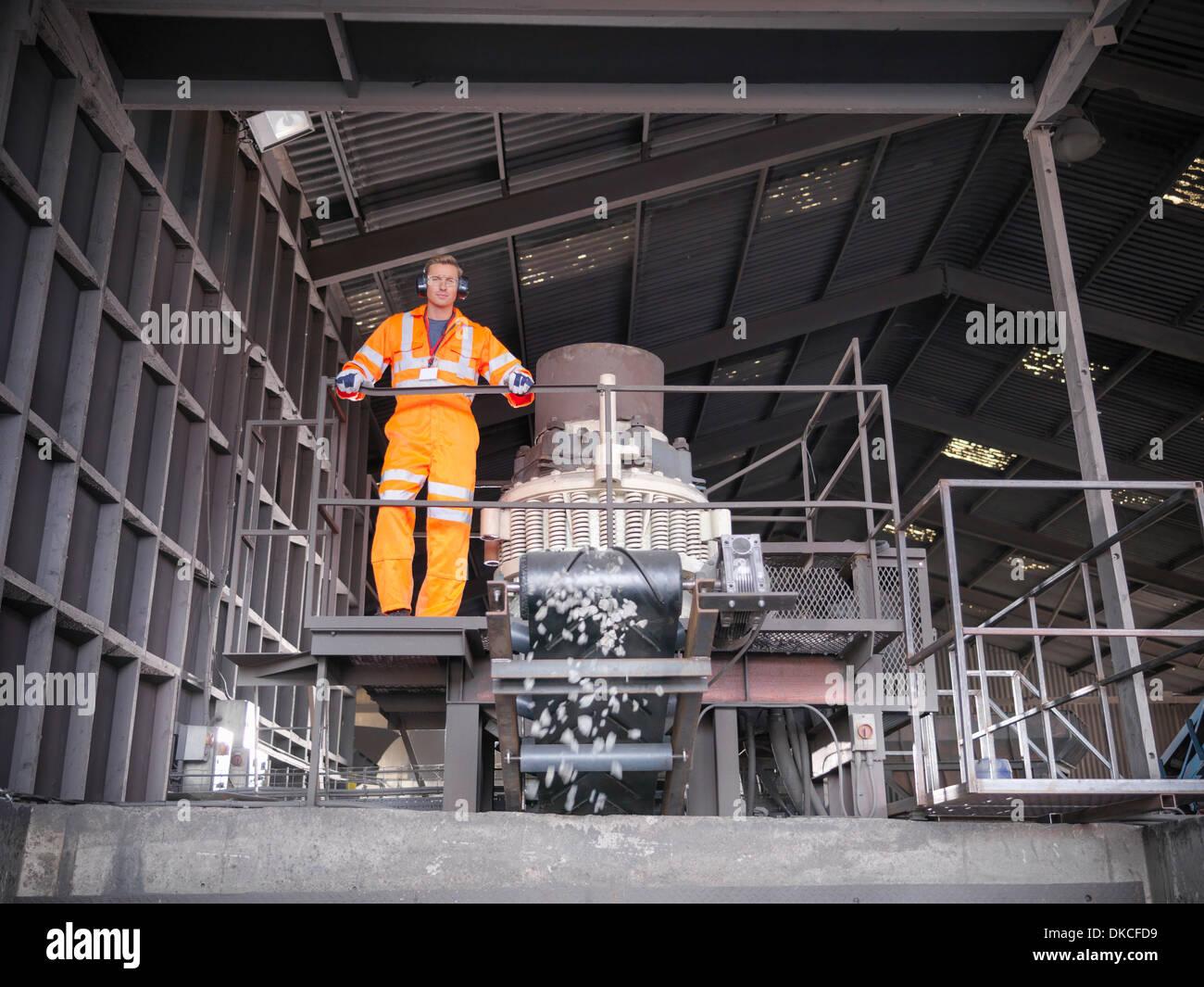 Arbeiter in der reflektierenden Arbeitskleidung Metall vernichtende Maschine in Betrieb Stockfoto