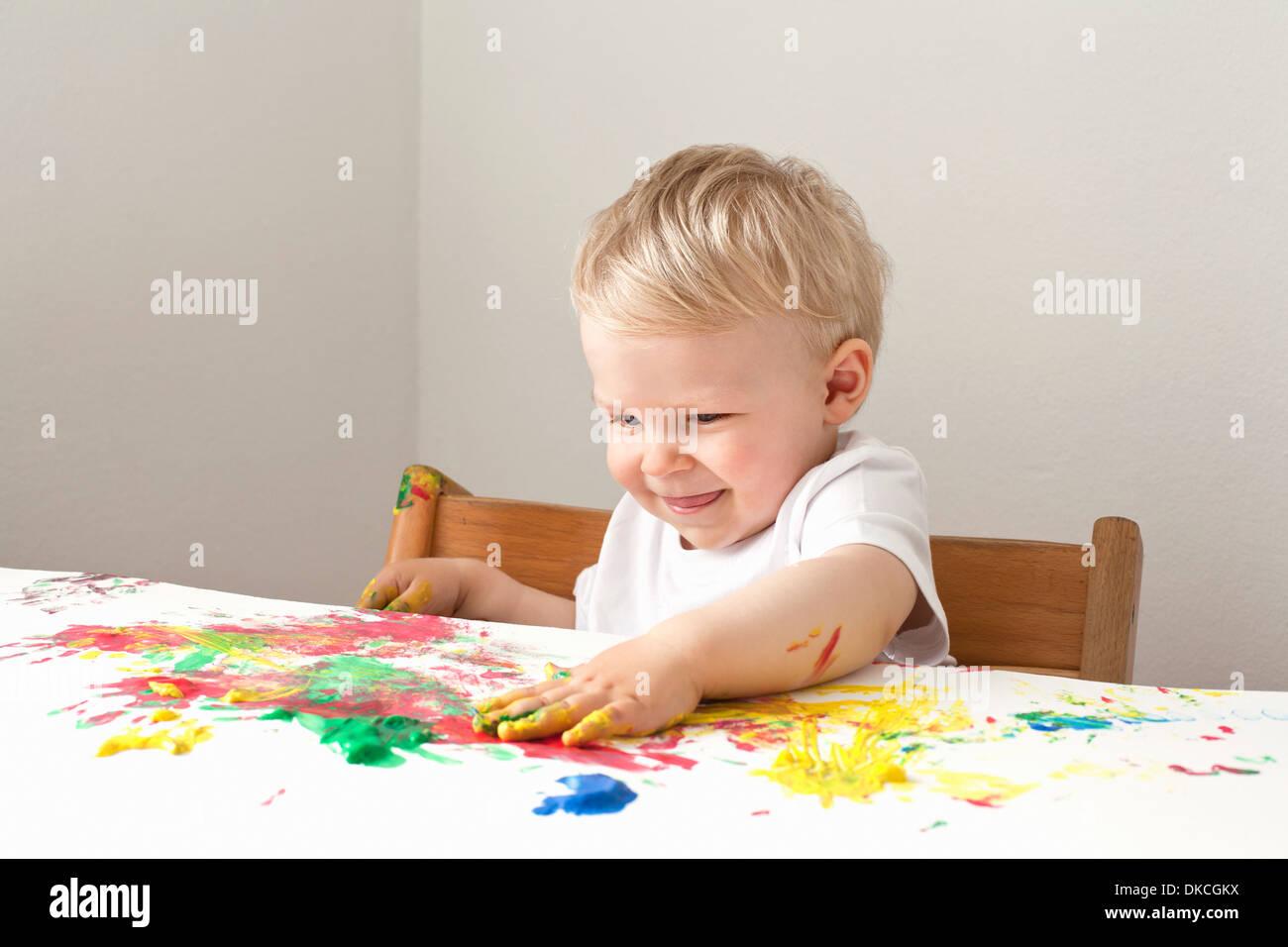 Kleiner Junge spielt mit Fingerfarben Stockbild
