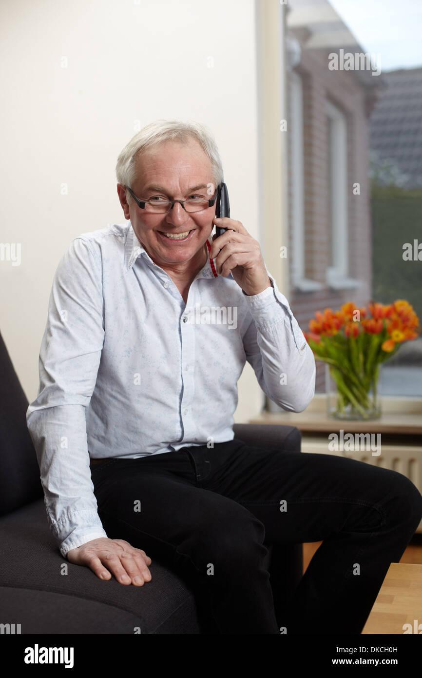 Ältere Mann zu Hause telefonieren mit Handy Stockfoto