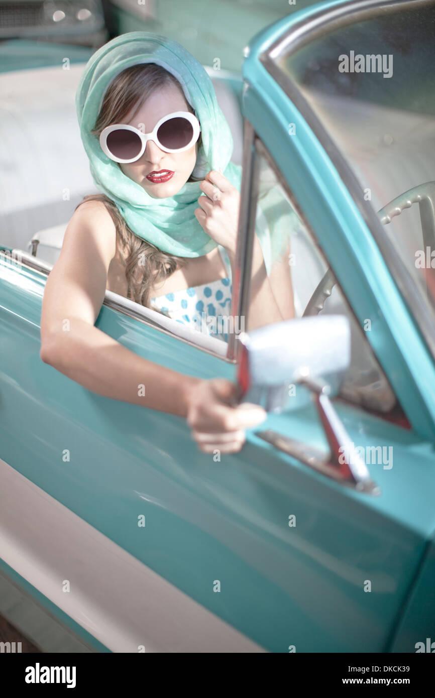 Frau mit Kopftuch und weiße Sonnenbrille im Oldtimer Cabrio Stockbild