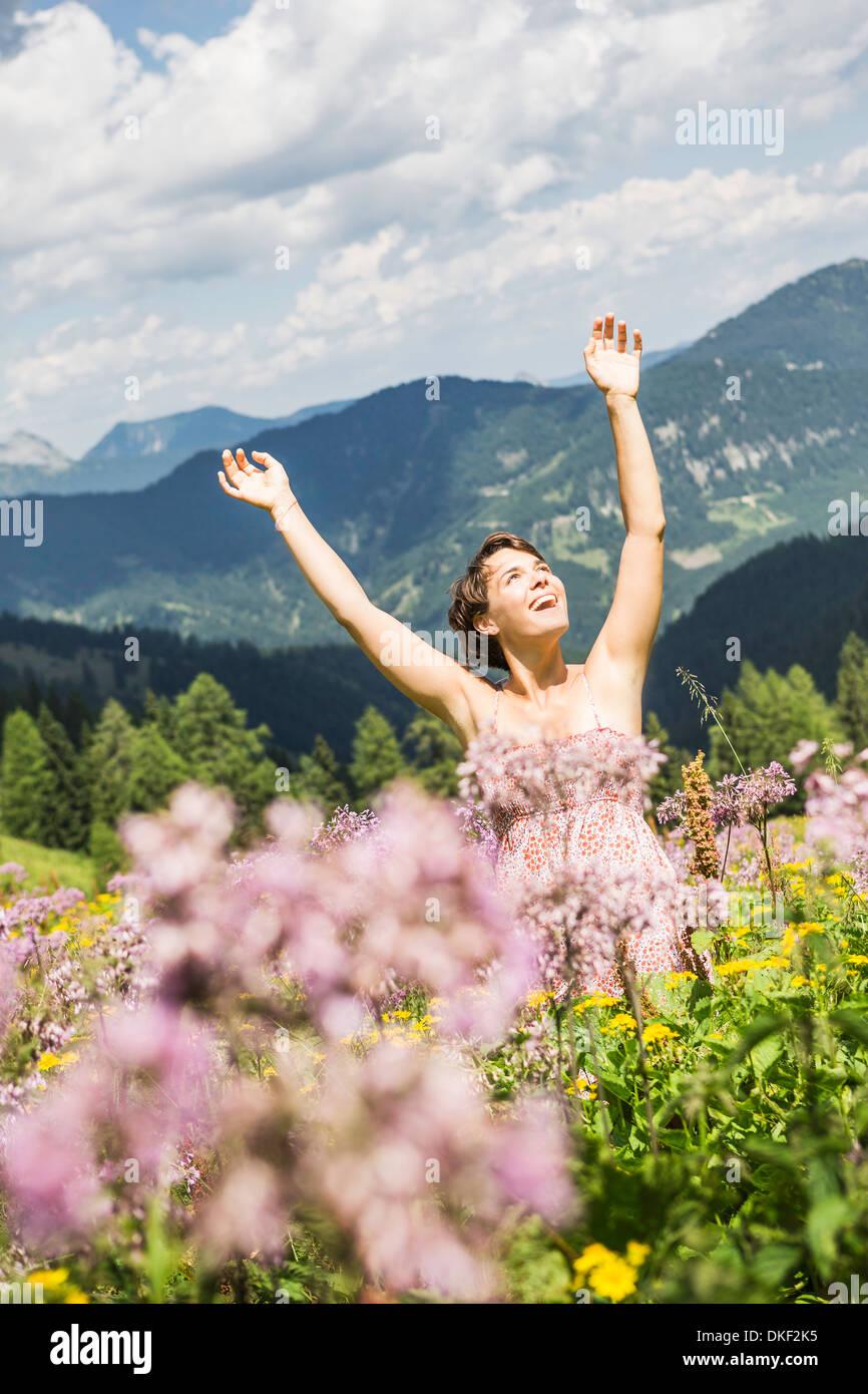 Porträt der jungen Frau mit Arme nach oben, Tirol, Österreich Stockbild