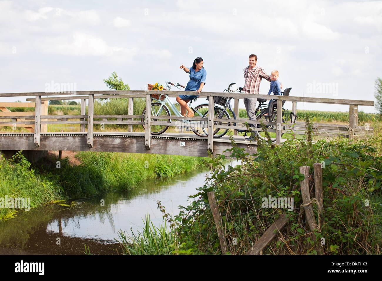 Familie Radfahren über Holzbrücke Stockbild