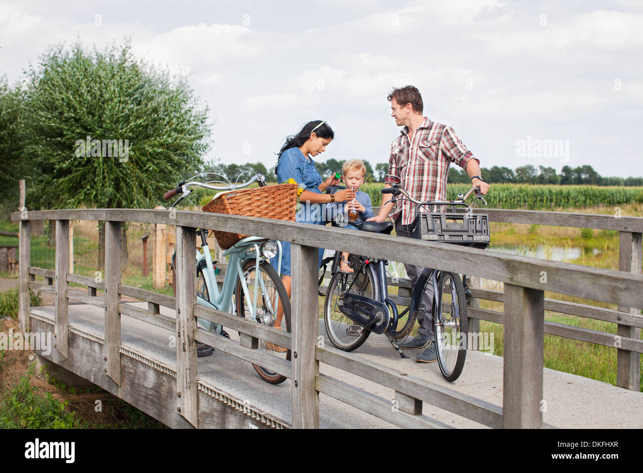 Familie auf Fahrrädern auf Holzbrücke, hielten zum trinken Stockbild