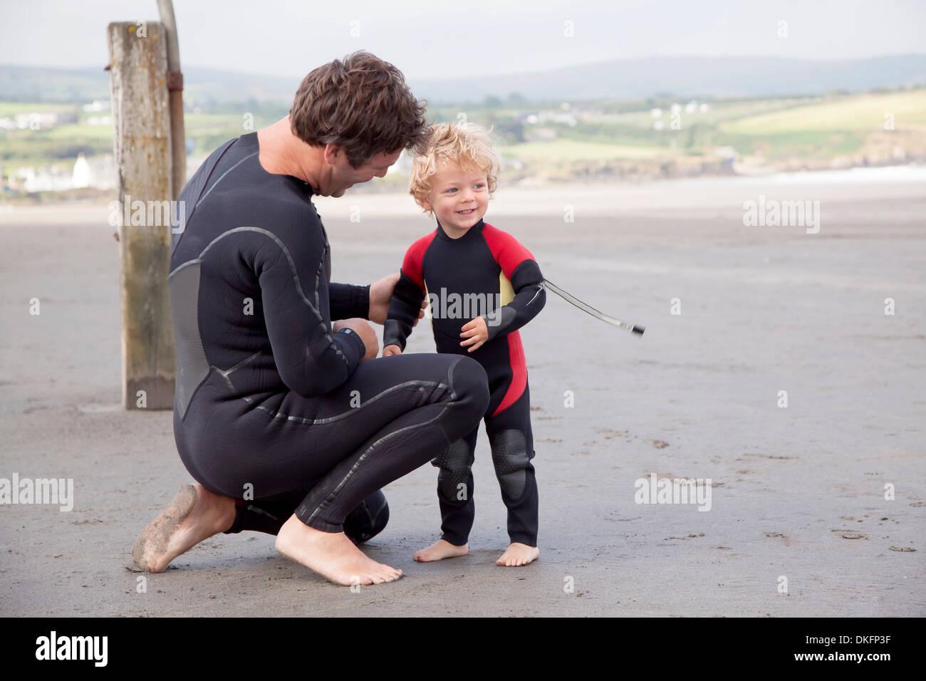 Vater und Sohn am Strand tragen Neoprenanzüge Stockbild