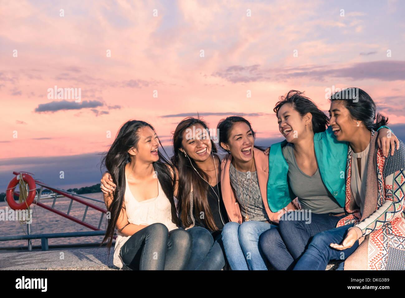 Junge Frauen liegen am Wasser sitzen in der Abenddämmerung mit Arme um Stockbild