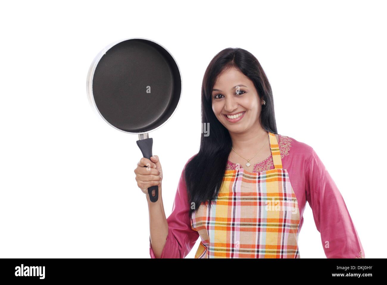 Junge indische Frau hält Küchenutensil vor weißem Hintergrund Stockbild