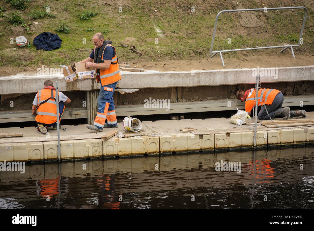 Drei Arbeiter arbeiten Männer bei der Arbeit tragen orange hi-Vis Westen, Inspektion oder Wartung eine konkrete Stockfoto