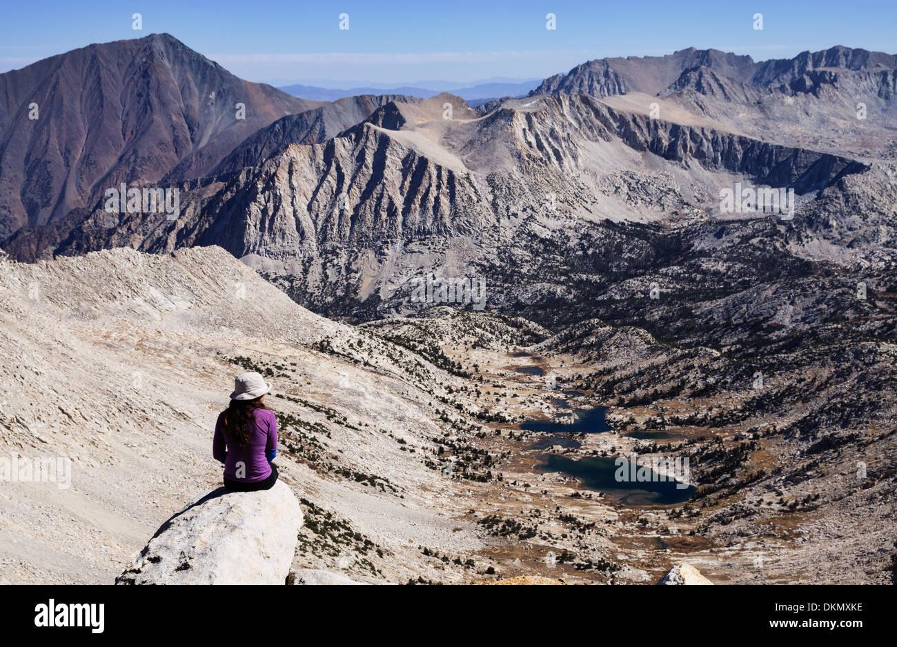 Frau sitzt auf einem Berg mit Blick auf die Sierra Nevada Berge betrachten Stockbild