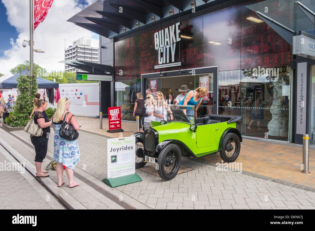Touristen fotografieren mit einer alten Austin Seven in der Container-Mall, Christchurch, Neuseeland. Die Quake Stockbild