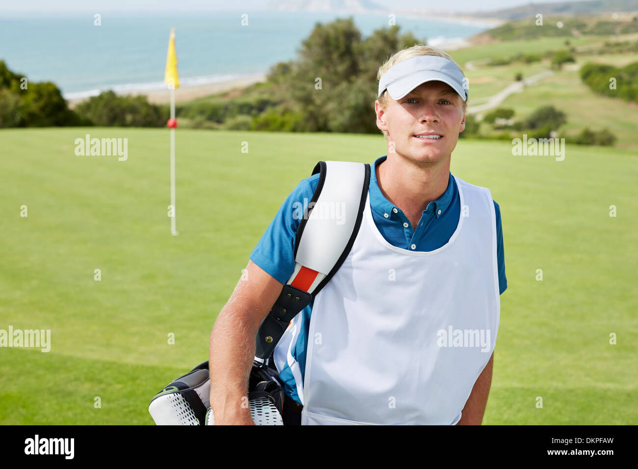 Caddy lächelnd auf Golfplatz Stockbild