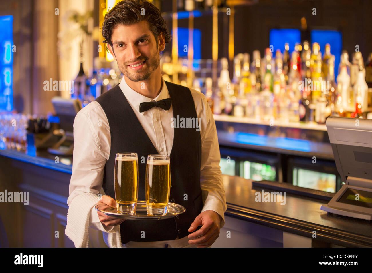 Porträt von gut gekleidete Barkeeper tragen Biere auf Tablett Stockbild