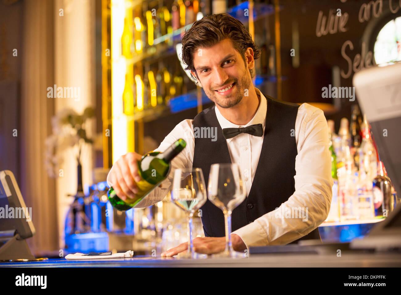 Porträt von gut gekleidete Barkeeper Gießen Wein in Luxus bar Stockbild