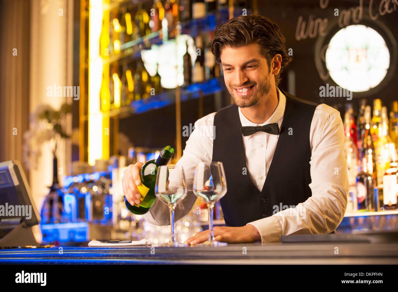 Gut gekleidete Barkeeper gießt Wein Stockbild
