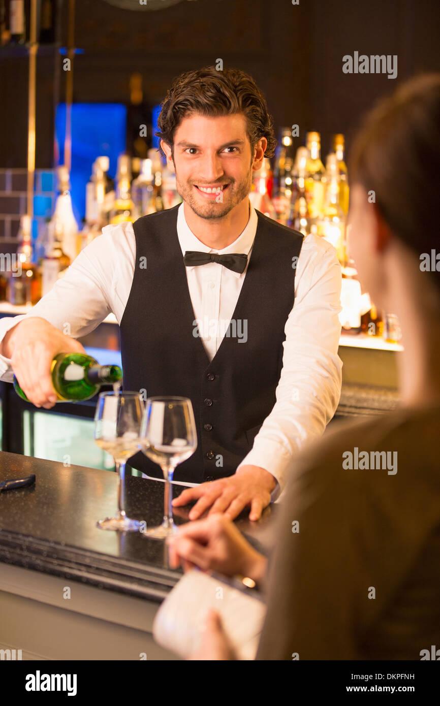 Gut gekleidete Barkeeper gießt Wein für Kunden in Luxus bar Stockbild