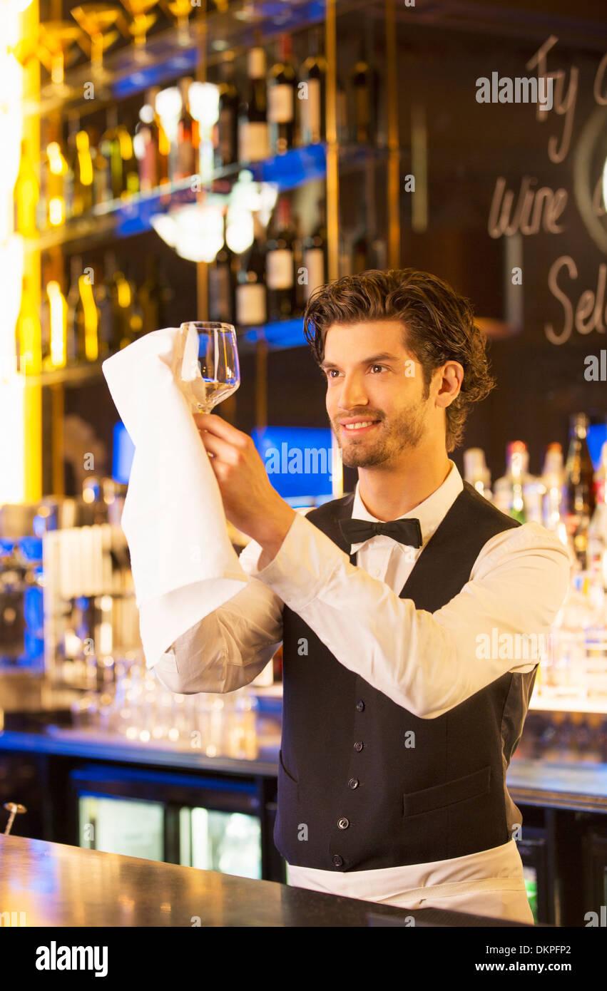 Gut gekleidete Barkeeper abwischen Weinglas in Luxus bar Stockbild