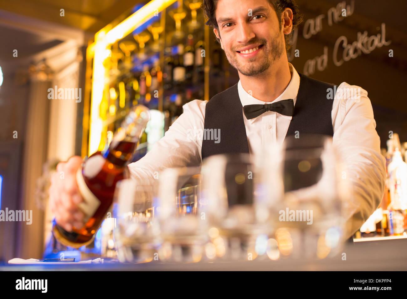 Porträt von gut gekleidete Barkeeper Gießen Bourbon in Luxus bar Stockbild