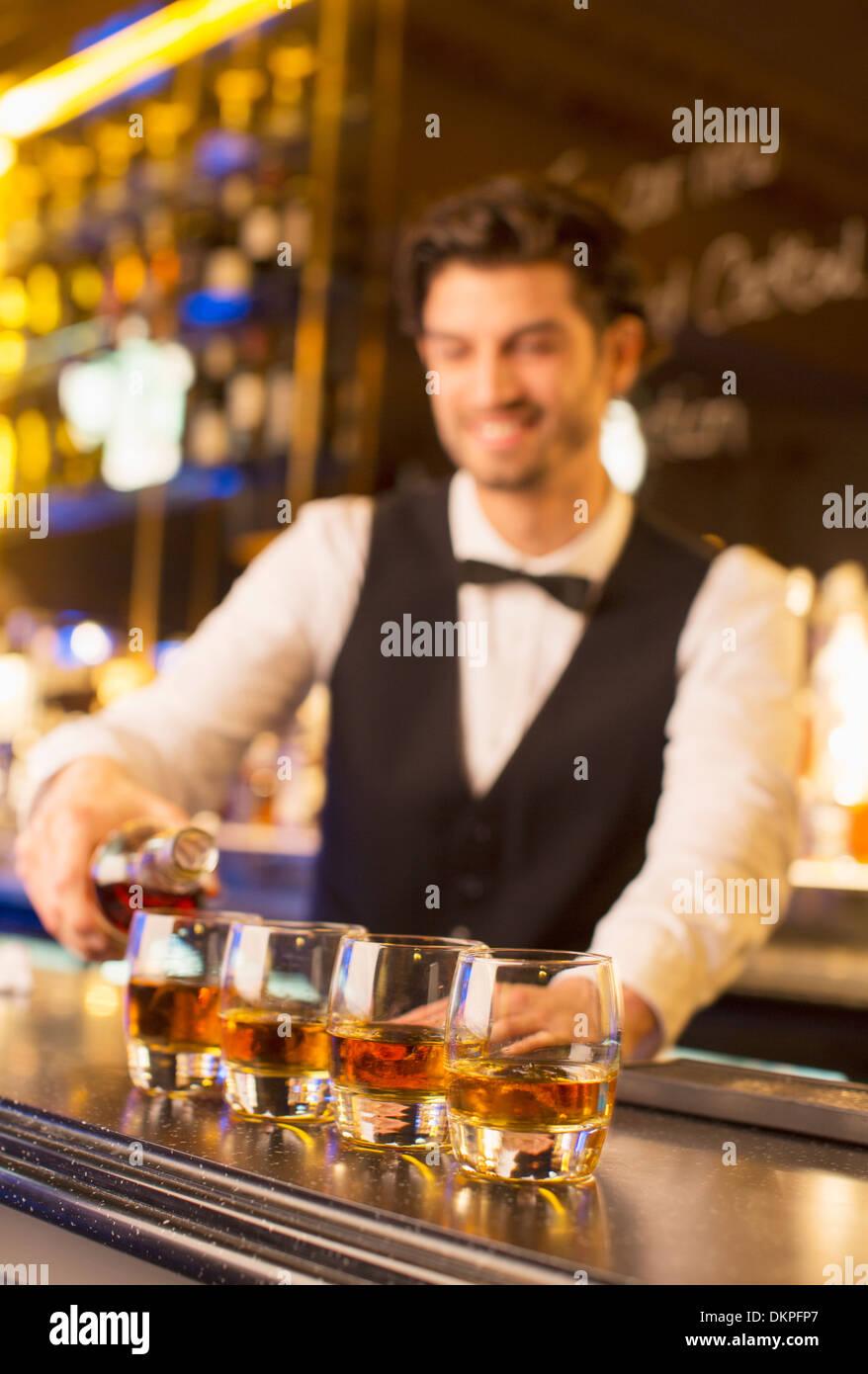Gut gekleidete Barkeeper Gießen Bourbon in Luxus bar Stockbild