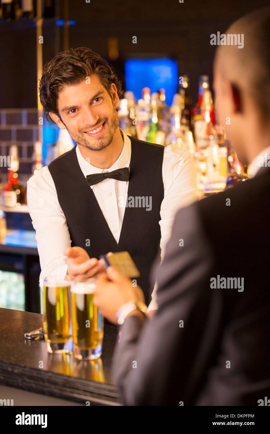 Gut gekleidete Barkeeper die Kreditkarte von Kunden in Luxus bar Stockbild