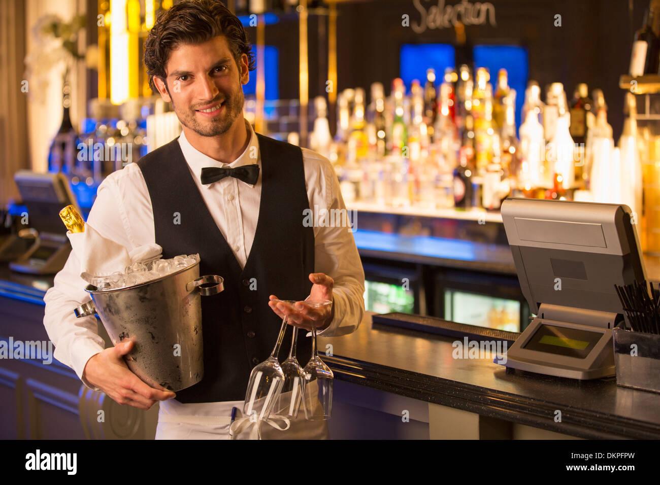 Porträt von gut gekleidete Barkeeper Holding Champagner Eimer in Luxus bar Stockbild