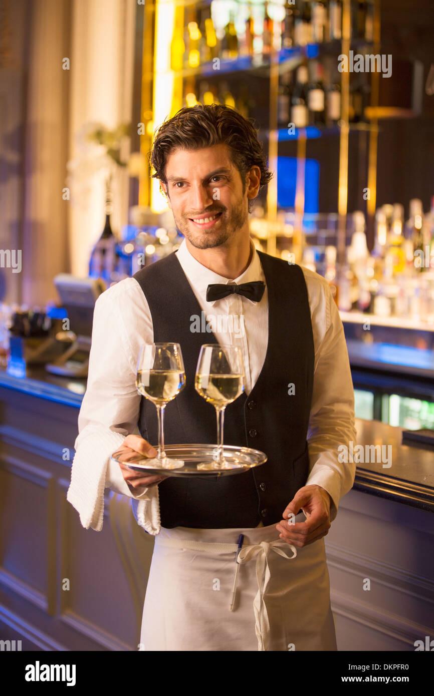 Gut gekleidete Barkeeper tragen Weingläser auf Tablett in Luxus bar Stockbild
