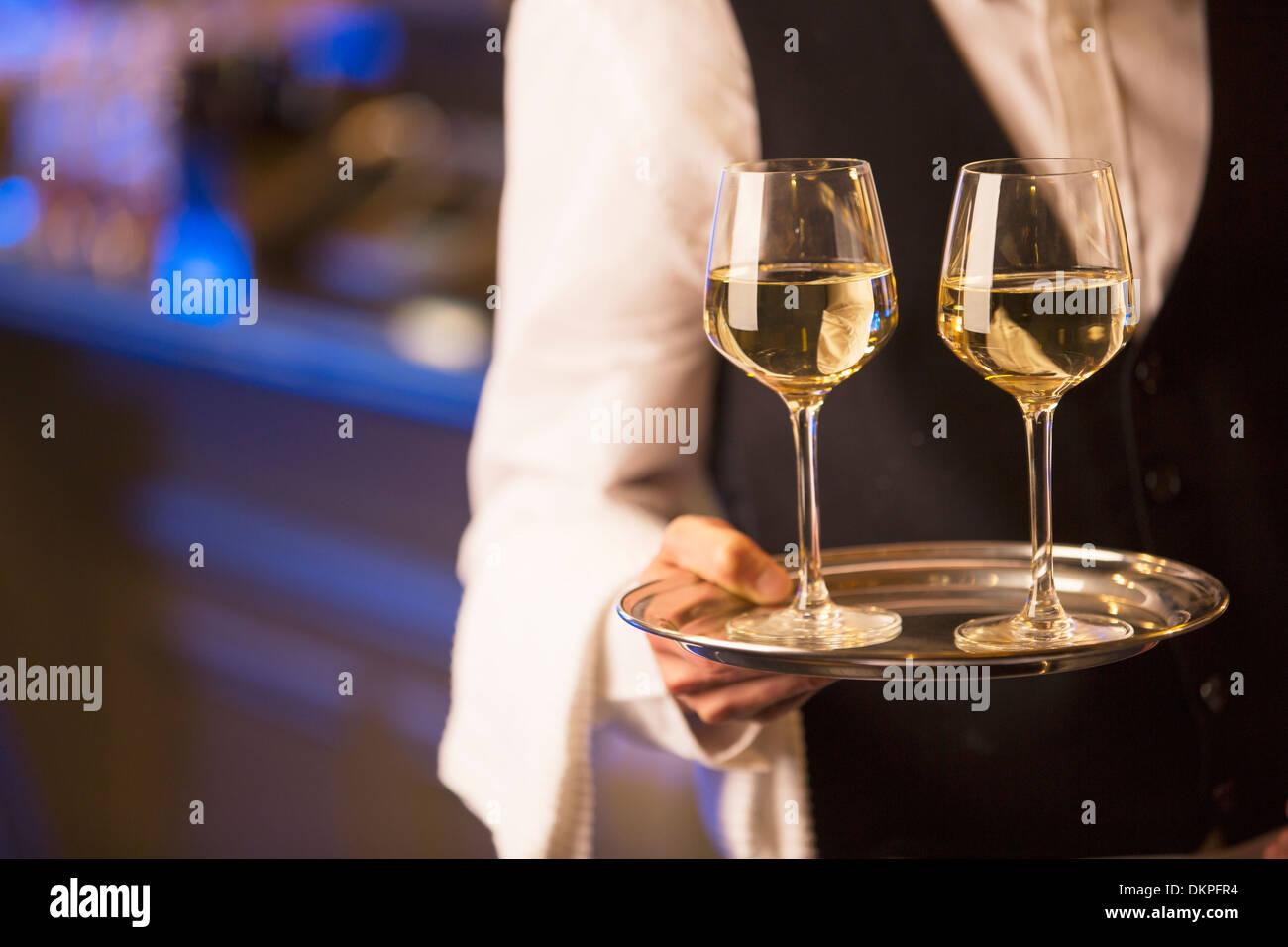 Nahaufnahme der Barkeeper tragen Weißweingläser auf Tablett Stockbild