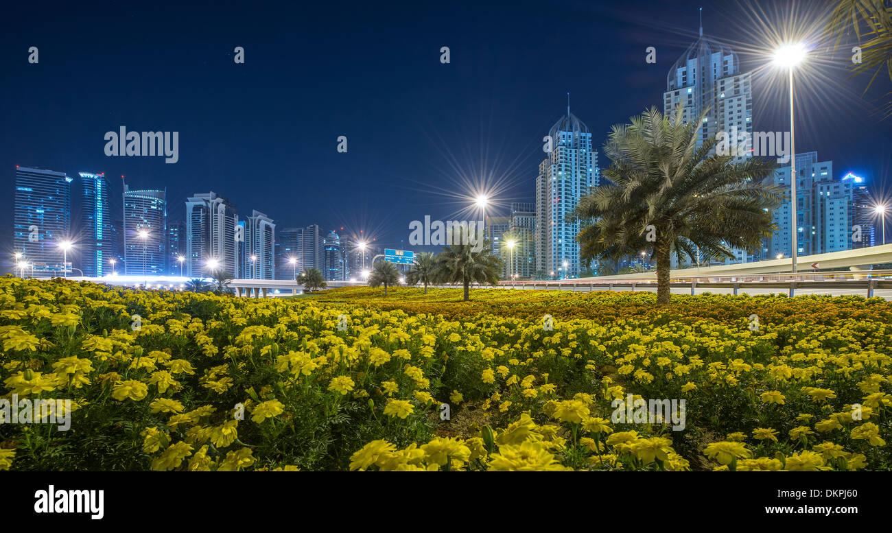 Blumen und Palmen auf einer Verkehrsinsel eines Kreisverkehrs an der Sheikh Zayed Road in der Nacht, Marina, neue Dubai, Vereinigte Arabische Emirate Stockbild
