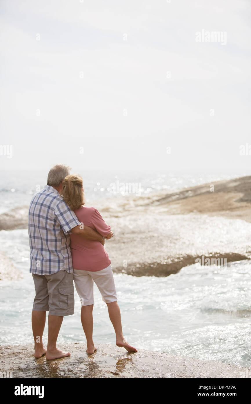 Älteres Ehepaar umarmt am Strand Stockbild