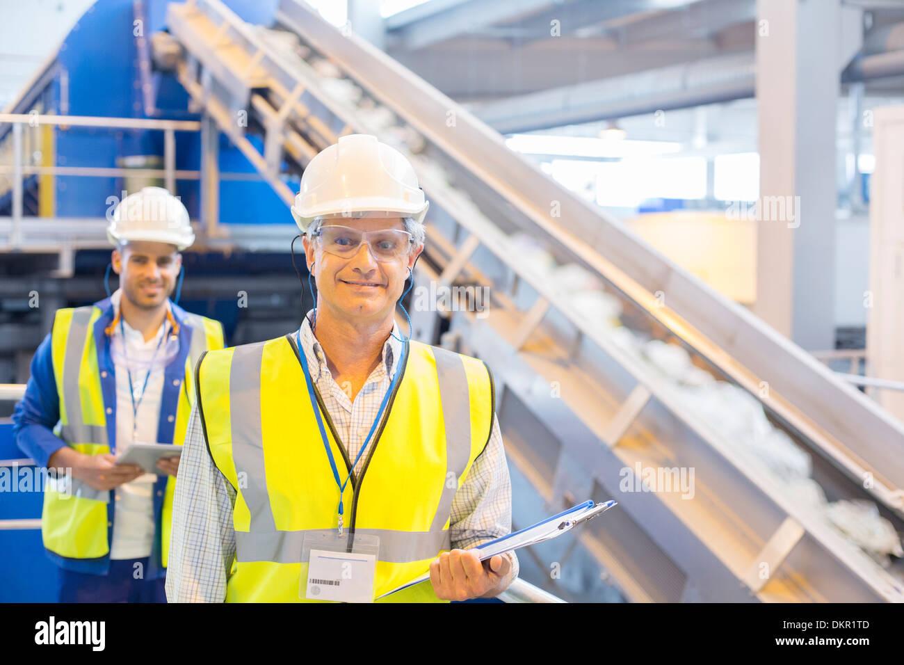 Arbeitnehmer, die lächelnd im recycling-center Stockfoto