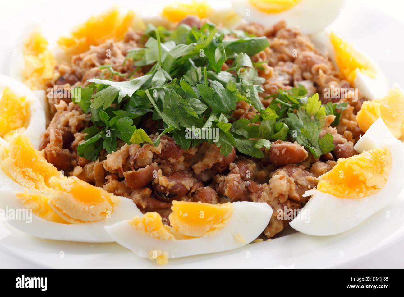 Ägyptische Foul- oder Ful - Medames auf eine Platte Garneshed mit Scheiben von gekochten Ei und glatte Petersilie. Stockbild