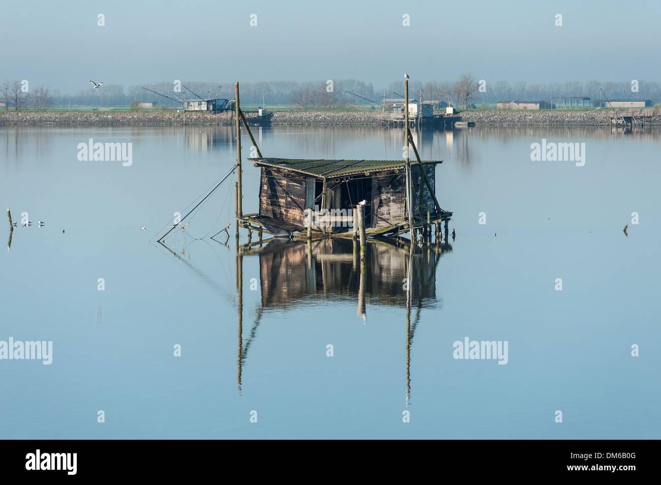 Verfallene Fischerhütte in einer Lagune, mit Reflexionen, Po-Fluss-Delta, Comacchio, Emilia-Romagna, Italien Stockbild
