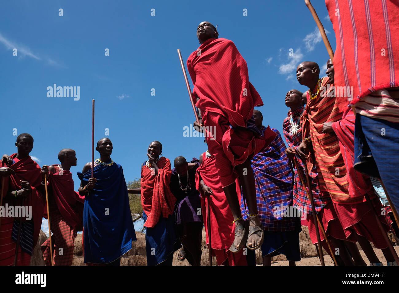Eine Gruppe von Massai Männer, die sich an der traditionellen Adumu Tanz allgemein bekannt als das Springen Tanz in einem kommenden alt Zeremonie für junge Krieger in der Masai Stamm in der Ngorongoro Conservation Area im Krater im Hochland von Tansania Ostafrika durchgeführt Stockfoto