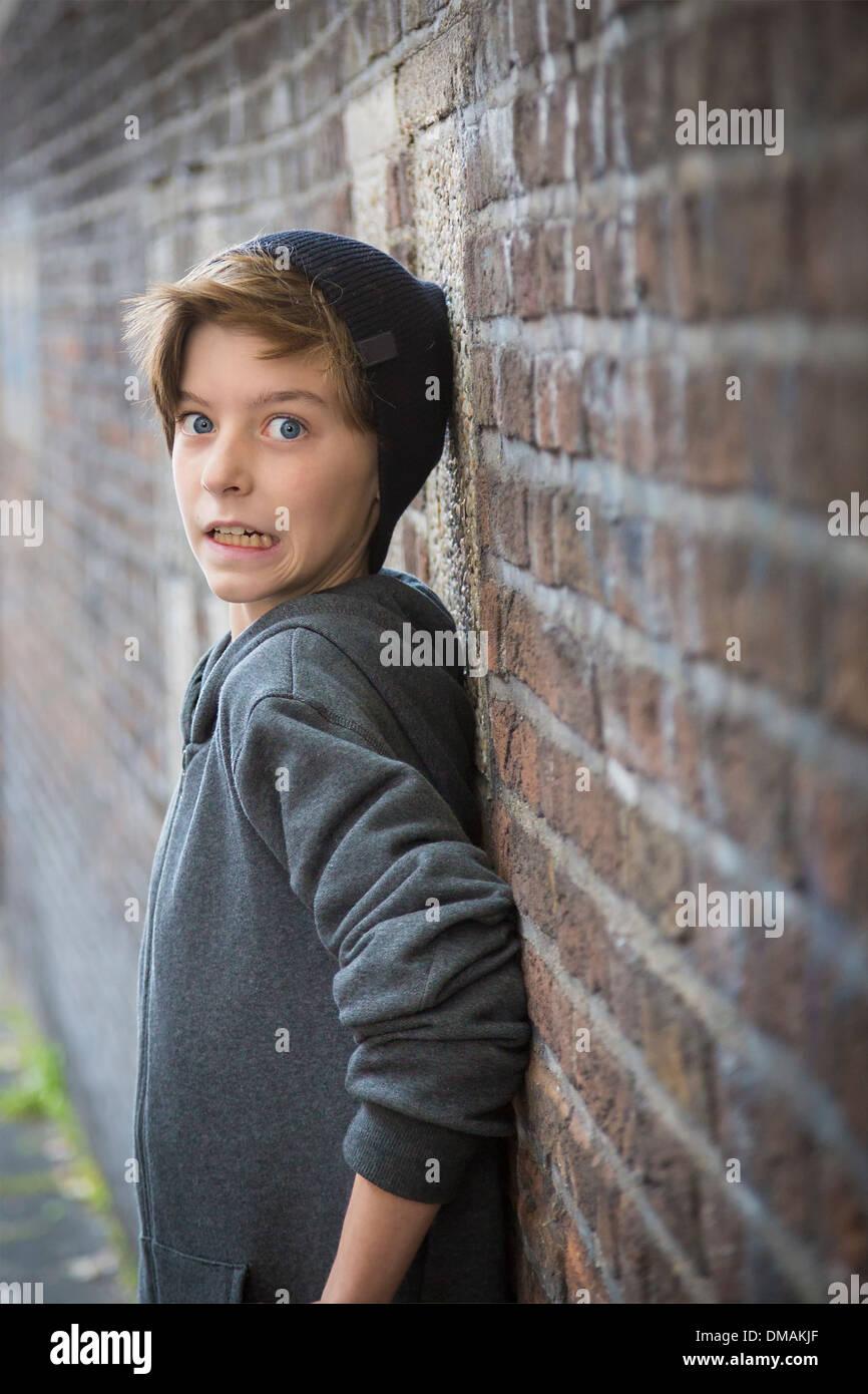 erschrocken Teenager junge an eine Wand gelehnt. Stockbild