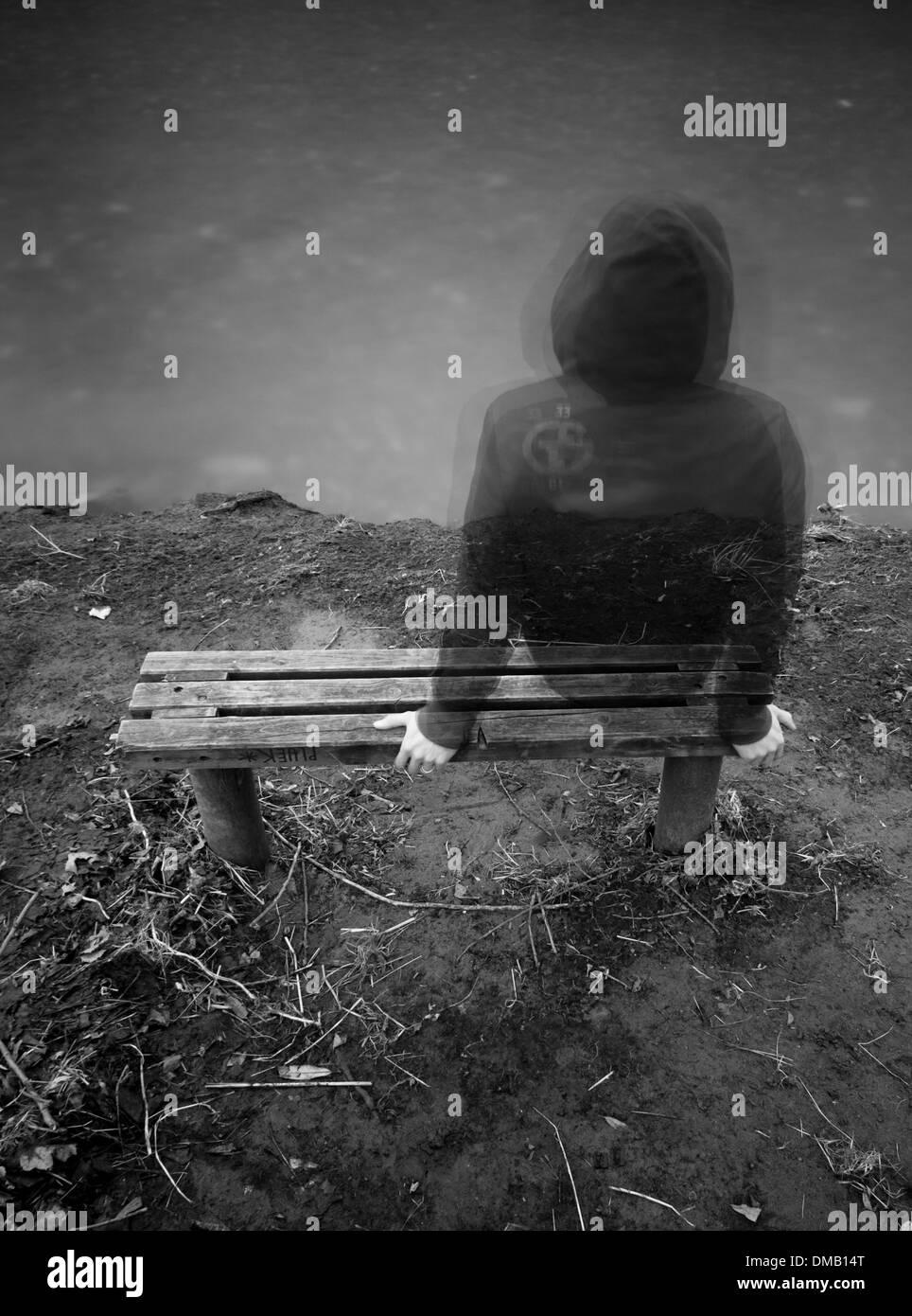 Mann allein auf einer Bank sitzend Stockbild