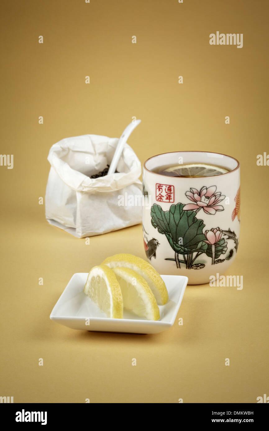 Tasse grüner Tee mit frischen Zitronenscheiben Stockbild