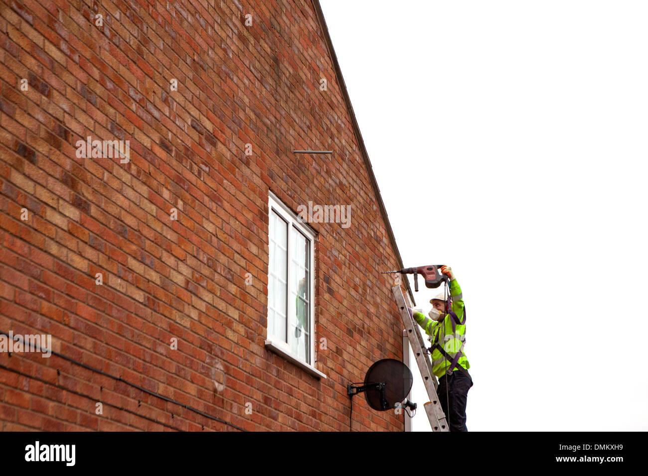 Geblasen in Wärmedämmung an einem bestehenden Gebäude durch ein Installationsprogramm als Bestandteil der Regierungen Stockfoto