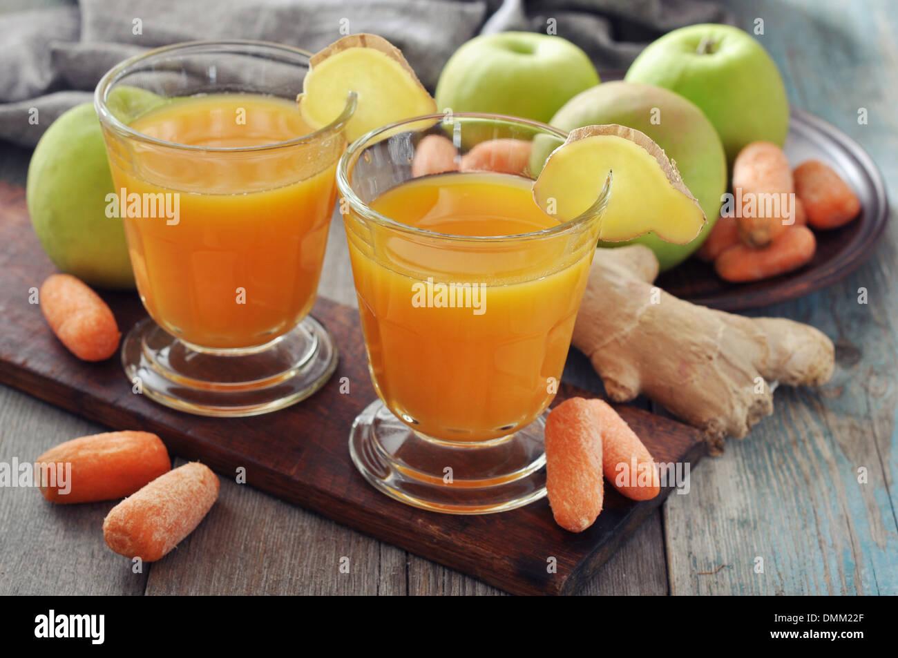 Apfel und Karotte Saft im Glas mit Ingwer, frischem Gemüse