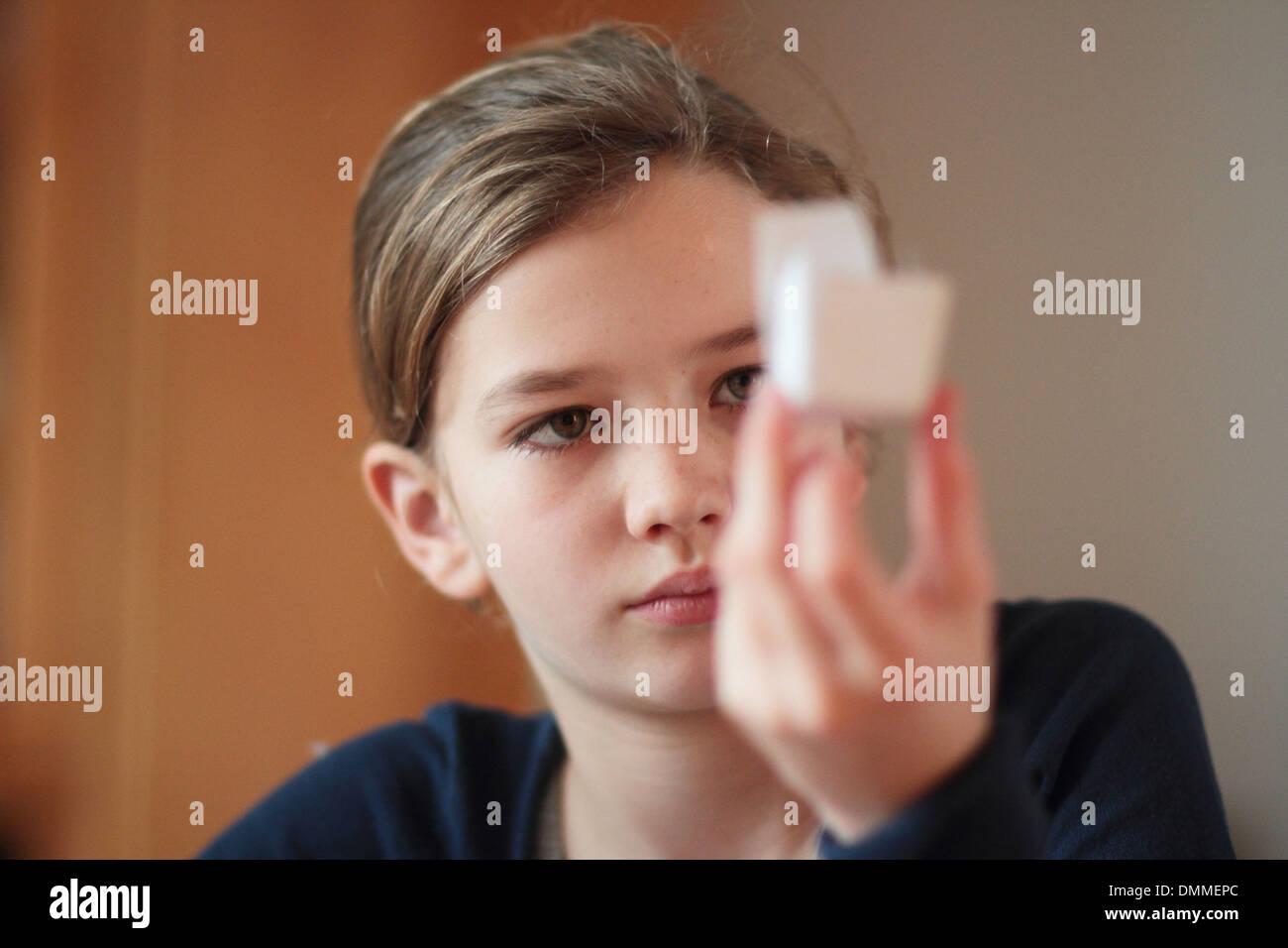 Mädchen in einem Raum sitzen und auf ein Papier-Modell Stockbild