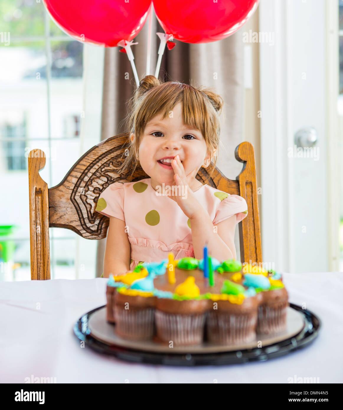 Glückliches Mädchen sitzen vor Geburtstagstorte Stockbild