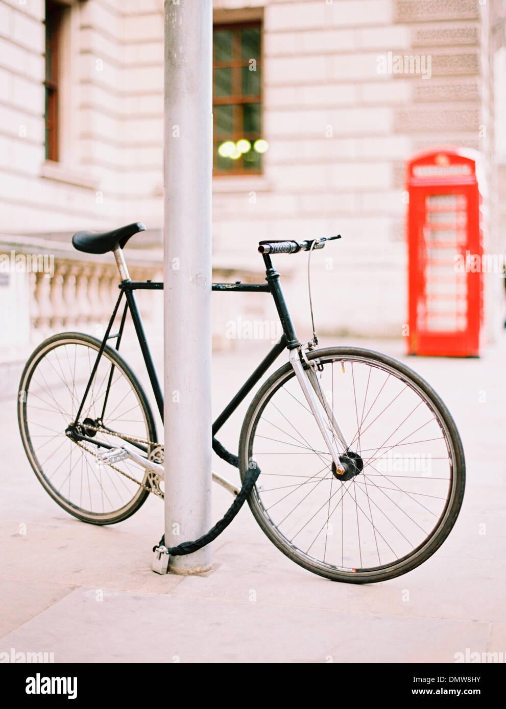 Ein Fahrrad gefesselt und an einen Laternenpfahl auf einer Londoner Straße gesperrt. Eine rote öffentliche Telefonzelle im Hintergrund. Stockbild