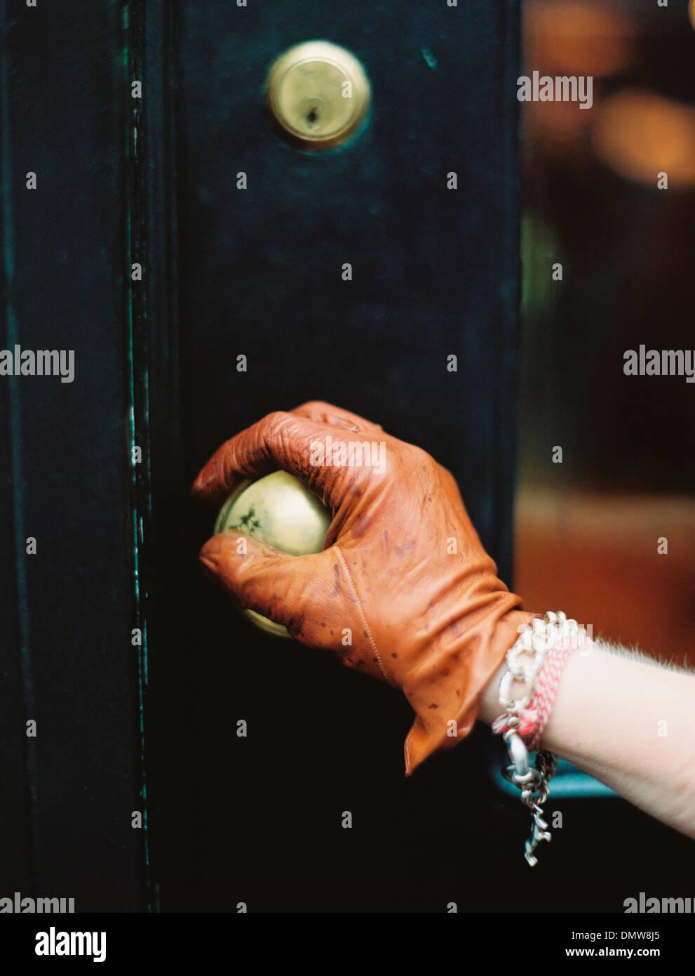 Eine Person trägt einen Lear-Handschuh, eine Tür zu öffnen. Stockbild
