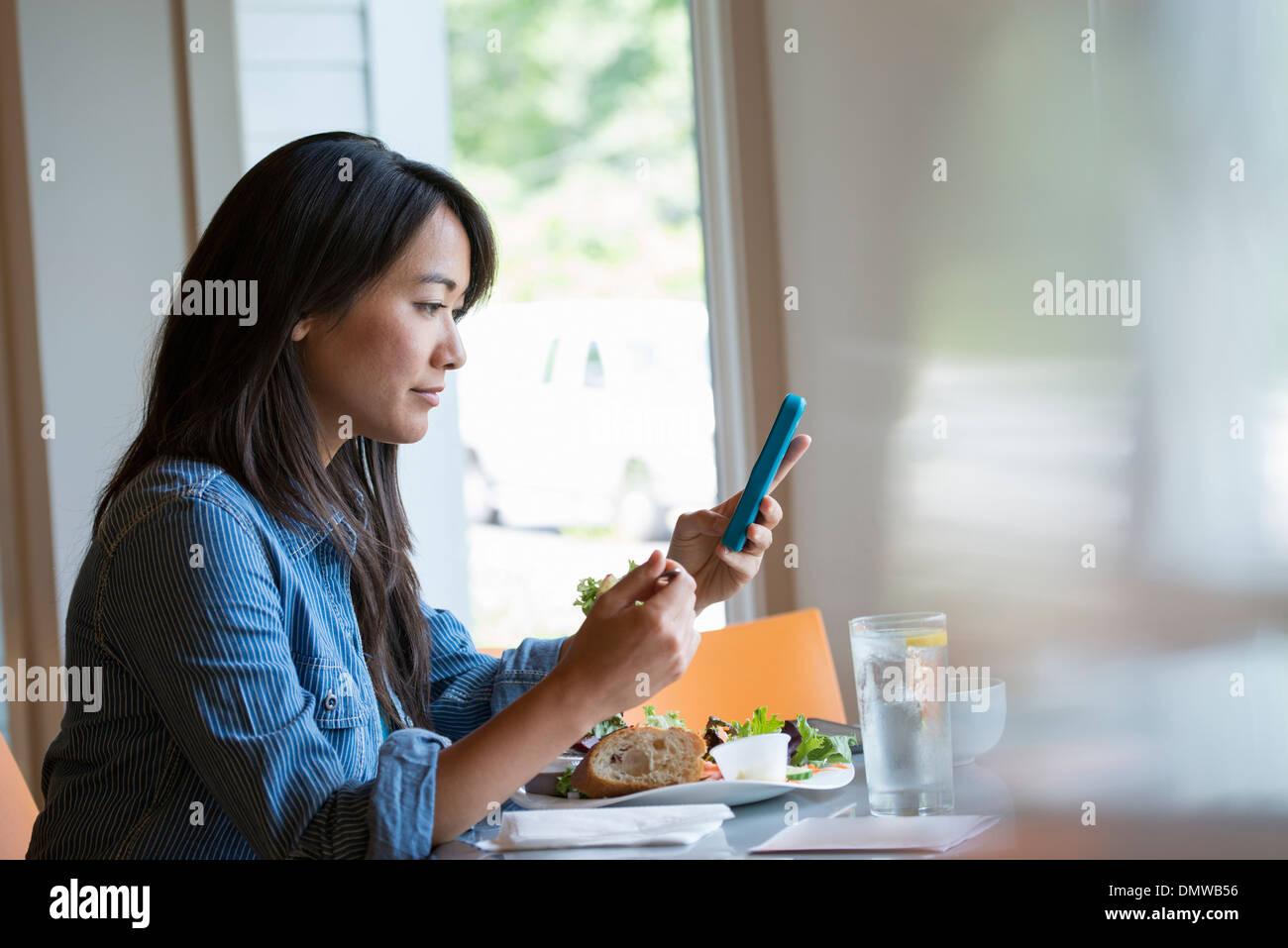 Eine Frau Essen einen Salat und überprüft ihr Telefon. Stockbild