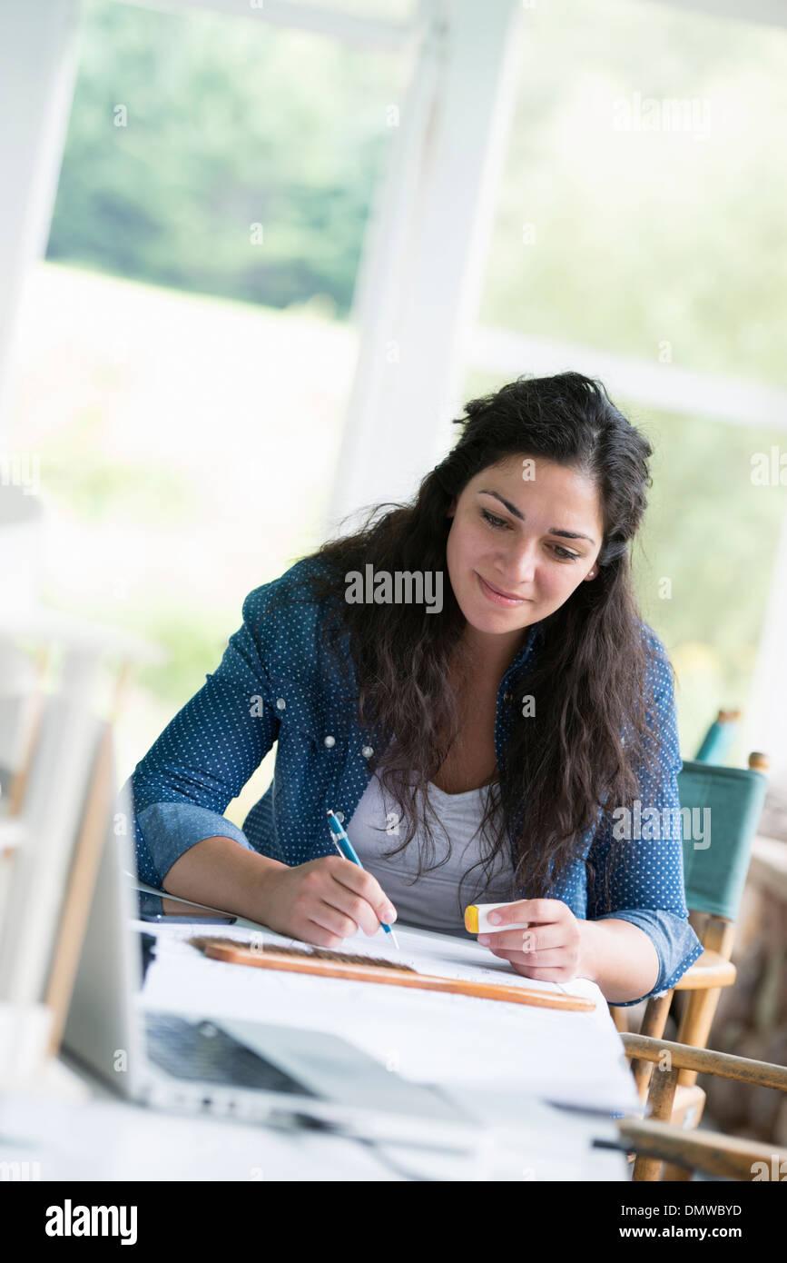 Eine Frau an einem Tisch mit einem digitalen Tablet arbeiten. Stockbild