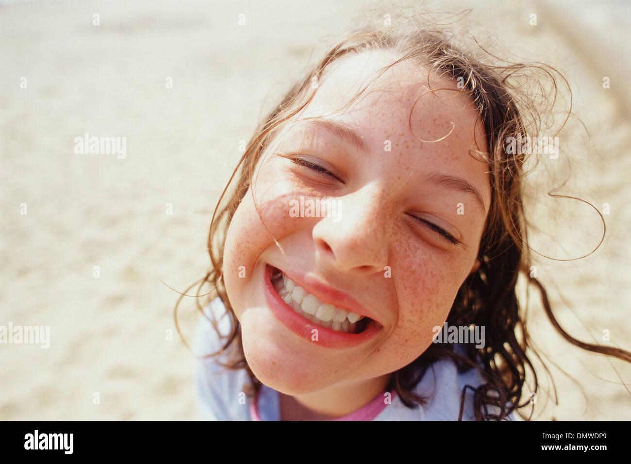 Ein junges Mädchen mit einem breiten Grinsen Augen halb geschlossen und nassem Haar draußen im Regen. Stockbild